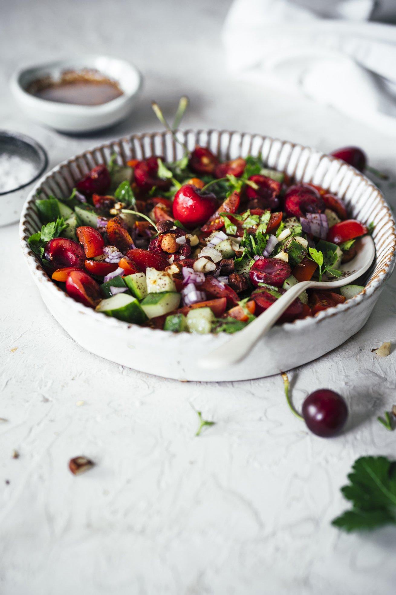 Tomaten. Gurken. Kirschen und Sumach. Zusammen in einem veganen Salat
